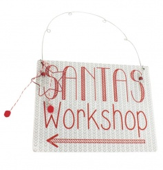 White and red nordic style Santas Workshop sign with decorative star, beads and pom poms.