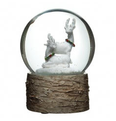 A large snow globe with a natural bark base and snowy winter reindeer scene.