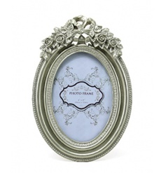 Oval picture frame in a champagne colour with floral design