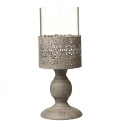 A chic candle holder with a decorative metal wrap with a cut out floral pattern.