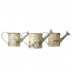 An assortment of vintage style watering cans with a mix of pretty flea market designs.