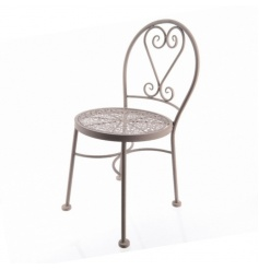 A beautiful iron kids sized chair with a decorative pattern.