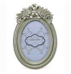 An oval shaped picture frame with an ornate design