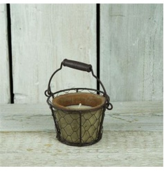 A rustic candle pot with citronella candle and wire basket carry.