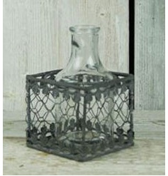 Decorative glass bottle inside a grey wash wire pot