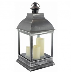 Flameless LED candles inside a distressed silver lantern