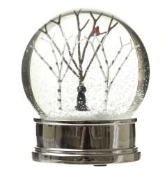 A charming snow globe with a black labrador ornament set within a winter scene.