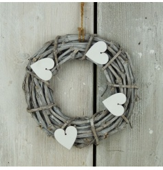 A shabby chic style wicker wreath with white heart decorations.