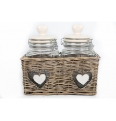 A wicker basket containing two glass storage jars with heart lids and hanging heart details.