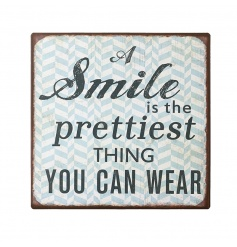 A shabby chic metal sign reading 'A Smile Is The Prettiest Thing You Can Wear'.