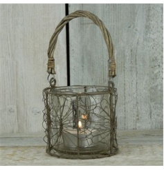 A rustic style floral lantern with wicker handle.