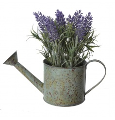 Rustic watering can with artificial lavender plant inside