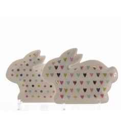 A mix of two rabbit shaped plates in multi-coloured heart and polkadot designs.