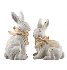 A mix of 2 charming wooden bunny ornaments with carved details. Finished with raffia bows.