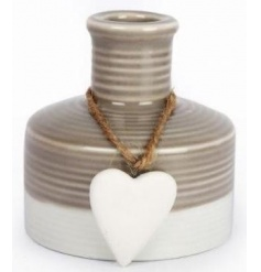 A shabby chic style decorative vase with a hanging heart detail. A charming decorative accessory for the home.