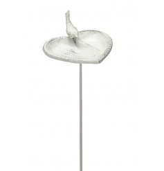 A white washed heart shaped bird bath with a decorative bird and stake to present in the garden.