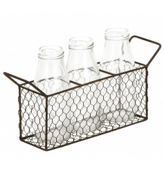 A set of 3 milk bottles set within a rustic chicken wire tray with handles.