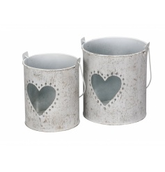 A set of 2 rustic lanterns, each with a heart cut out detail.