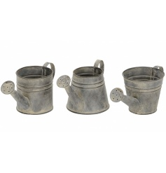 An assortment of 3 rustic watering cans in grey. Ideal for planting and for decoration.