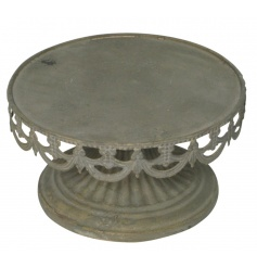 A rustic style cake stand with a decorative patterned base.