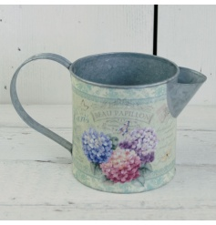 A rustic metal jug with a pretty hydrangea floral decal. A lovely planter.