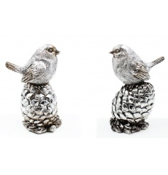 An assortment of 2 vintage style silver bird ornaments sat upon pinecones.