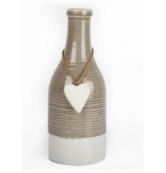 A shabby chic style ceramic bottle with a heart decoration. A stylish home accessory.
