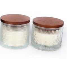 An assortment of 2 scented candles set within embossed glass jars with a wooden lid.
